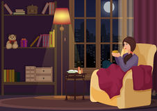 Young woman at home sitting in soft chear relaxing in her living room and drinking coffee or tea. Girl rests in night. Interior Stock Photo