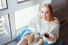 Young woman at home sitting on window sill winter concept drinking tea reading book Stock Photos