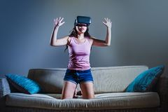 Young woman at home sofa couch playing video game using VR virtual reality goggles watching in 3 dimension enjoying curious having. Young woman at home sofa royalty free stock photo