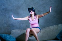 Young woman at home sofa couch playing video game using VR virtual reality goggles watching in 3 dimension enjoying curious having. Young woman at home sofa stock image