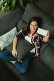 Young woman at home on the sofa with the mobile Stock Photos
