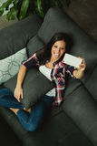 Young woman at home on the sofa with the mobile Stock Images