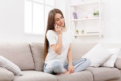 Young woman at home talking on mobile on beige couch in light livingroom. Brunette girl at home talking on mobile on beige couch in light livingroom, copy space Stock Photography
