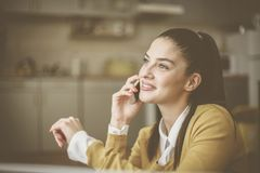 Young woman at home talking on mobile phone. royalty free stock images