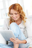 Young woman at home with touchpad Stock Photos