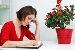 Young woman at home writing Stock Images