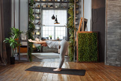 Young woman in homeware practicing balance yoga pose on carpet in her comfy bedroom. Stock Image