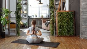 Young woman in homeware practicing balance yoga pose on carpet in her comfy bedroom. Stock Photo