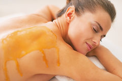 Young woman with honey on back laying on massage table Royalty Free Stock Image