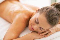 Young woman with honey on back laying on massage table Royalty Free Stock Photography