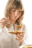 Young woman with honey and bread Royalty Free Stock Photos
