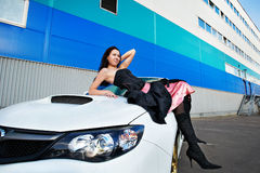 Young woman on hood of a white sports car Royalty Free Stock Photo