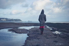 Young woman in hooded coat walking on beach Stock Image