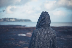 Young woman in hooded coat walking on beach Royalty Free Stock Photo