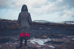 Young woman in hooded coat walking on beach Royalty Free Stock Image