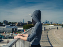 Young woman in hoodie by fence in city Stock Images