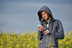 Young woman in hoodie using her smart phone in the outdoors Royalty Free Stock Image