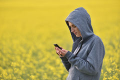 Young woman in hoodie using her smart phone in the outdoors Royalty Free Stock Images