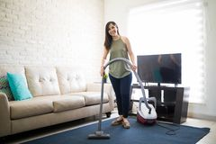 Young woman hoovering carpet with vacuum cleaner. Full length of a beautiful young housewife cleaning house mat in living room using vacuum cleaner Stock Photography
