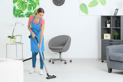Young woman hoovering floor. At home stock photo