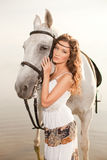 Young woman on a horse. Horseback rider, woman riding horse on b Stock Photo