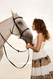 Young woman on a horse. Horseback rider, woman riding horse on b Royalty Free Stock Images