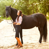 Young woman with a horse in park near the river Stock Photography