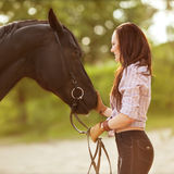 Young woman with a horse in park near the river Royalty Free Stock Photography