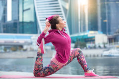 Young woman in Horse rider pose against the skyscrapers. Young attractive woman practicing yoga, standing in Horse rider exercise, variation of anjaneyasana pose royalty free stock image