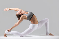 Young woman in Horse rider pose, grey studio background. Young attractive woman practicing yoga, standing in Horse rider exercise, anjaneyasana pose, working out royalty free stock photos