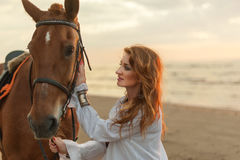Young woman with horse on sea cost Stock Photo