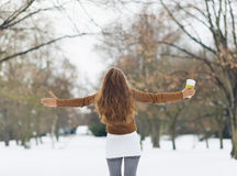 Young woman with hot beverage in winter park Royalty Free Stock Photography