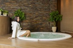 Young woman in the hot tub. Young woman sitting on the edge of the hot tub royalty free stock image