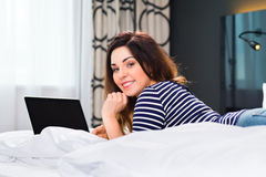 Young woman in Hotel in bed with wifi and computer Royalty Free Stock Photos