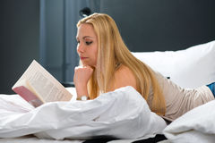 Young woman in Hotel reading book in bed Stock Images