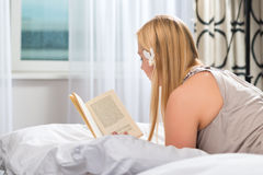Young woman in Hotel reading book in bed Royalty Free Stock Images