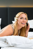 Young woman in Hotel reading book in bed Royalty Free Stock Image