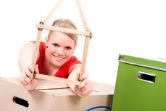 Young woman with house symbol. Young woman with a folding rule as a house symbol sits between move cardboards Royalty Free Stock Images