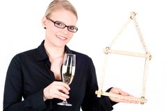 Young woman with house symbol and champagne glass Stock Photos