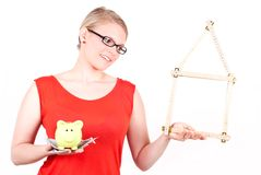 Young woman with house symbol and piggy bank. Young woman with folding rule as a house symbol and piggy bank before white background Royalty Free Stock Photo
