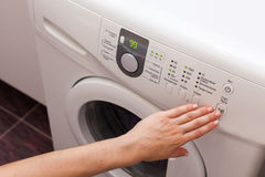 Young woman or housekeeper has a laundry day at home, she select the program. Royalty Free Stock Images