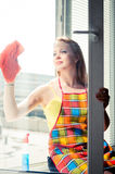 Young woman housewife washes a window Royalty Free Stock Image