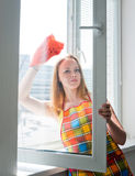 Young woman housewife washes a window Royalty Free Stock Photo