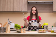 The young woman housewife working in the kitchen Stock Photos