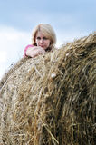 Young woman and huge haystack Stock Photo