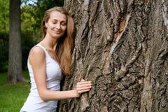 Young woman hugging big tree Stock Image