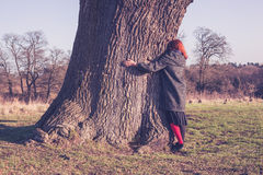 Young woman hugging a big tree in winter Stock Photos