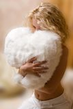 Young woman hugging cushion Royalty Free Stock Image
