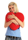 Young woman hugging a heart-shaped pillow Stock Photo