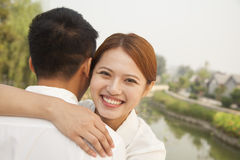 Young Woman Hugging Her Boyfriend Stock Image